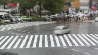 TL, MS, Tilt-Shift Crowds with umbrellas cross Hachiko crossing, Shibuya, in the rain / Tokyo, Japan