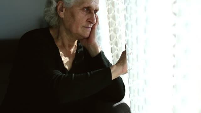 TiltUp: Senior woman portrait looking through window behind the curtain