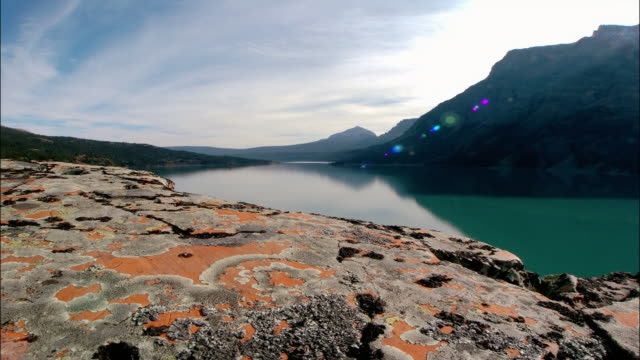 Time lapse aerial over lichen-covered rocks towards lake at foot of Rocky Mts / Glacier Nat'l Park, Montana