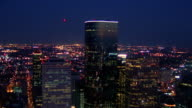 Time lapse aerial point of view over Houston skyline at night with traffic on highways / Texas