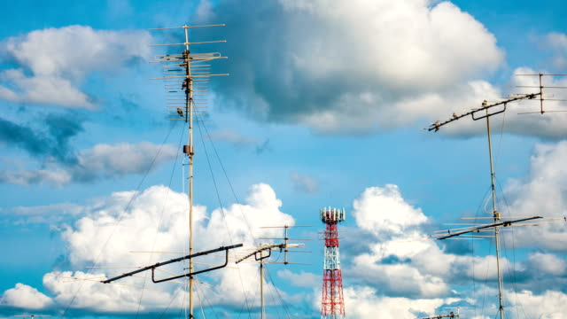 Time lapse : Aerial television antenna with cloud moving and blue sky, panning shot