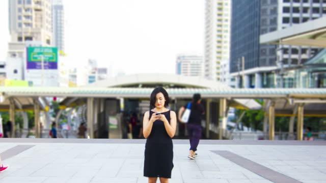 Zeitraffer: Asiatische Frau genießen, mit smartphone während Reisen Städtisches Motiv