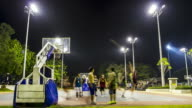 time lapse : Asian young adult playing Basketball outdoor night scene
