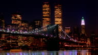 Time lapse boats and traffic on Brooklyn Bridge with World Trade Center in background at night / New York City