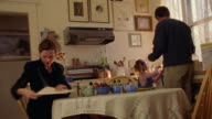 time lapse CANTED man serving coffee to businesswoman + helping girl get ready for school in kitchen
