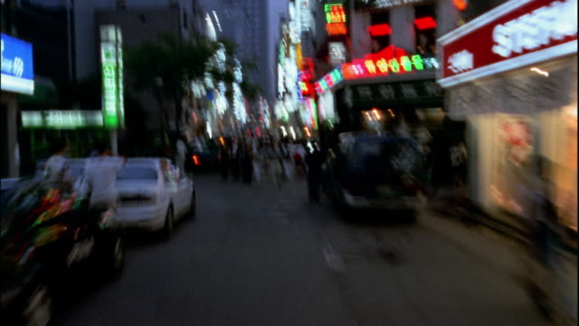 Time lapse car point of view city street crowded with pedestrians at twillight / Seoul, South Korea
