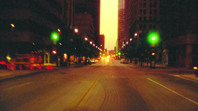 GRAINY time lapse car point of view driving on city streets through intersections at dusk / Dallas, Texas, USA
