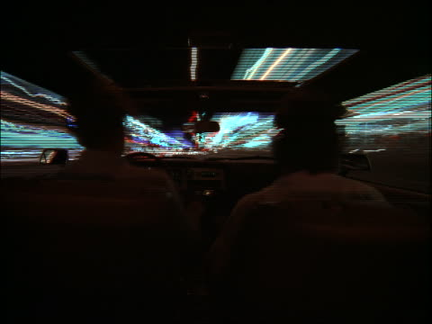 time lapse car point of view on city street at night / over men's shoulders