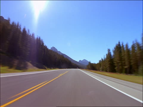 time lapse car point of view on country road through Livingston Mountain Range / Canadian Rockies