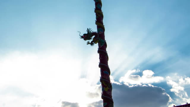 time lapse : Chinese dragon totem pole with sunbeam and cloud moving background