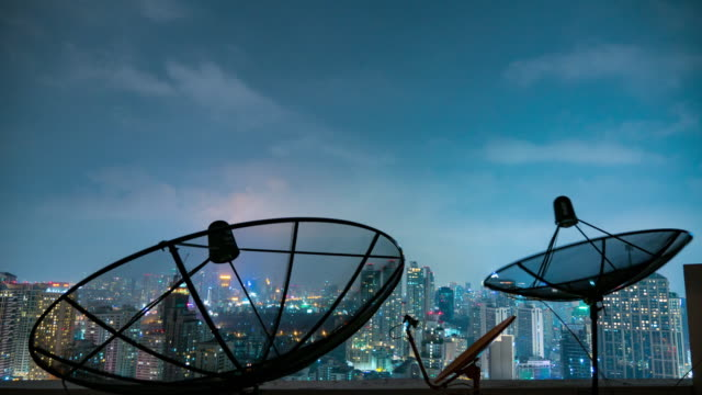Time lapse close up Parabolic satellite dish with building at night