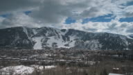 Time lapse clouds and shadows float over majestic snow-capped mountains.