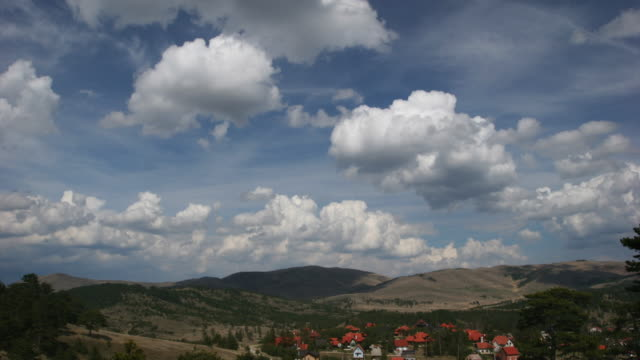Time lapse - clouds flies over mountain village