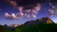 time lapse clouds moving over green mountains in foreground + snowcapped mountains in background / Aspen, Colorado