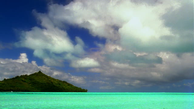 Time lapse clouds moving over ocean and island / Bora Bora, French Polynesia, South Pacific