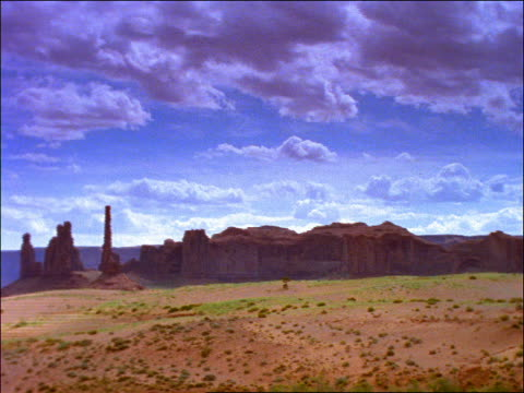PAN time lapse clouds over desert with rock formations / Monument Valley, Utah