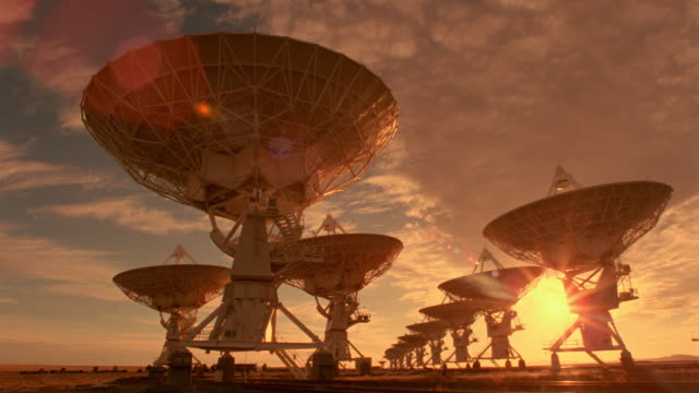 time lapse clouds over moving VLA radio telescope dishes at sunset / New Mexico