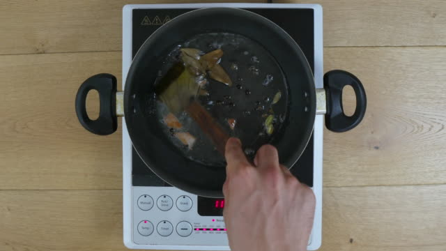 Time Lapse, Cook prepares Indian masala with whole spices and herbs on a cooking pan, including bay leaves, cloves, cinnamon, elaichi, cardamon,