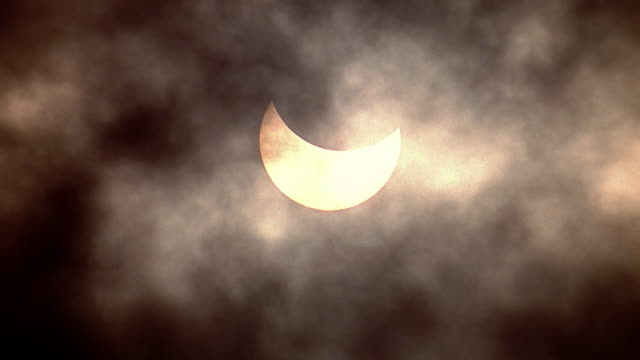 Time lapse dark clouds moving in front of partial solar eclipse / Hawaii