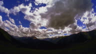 SEMI-FISHEYE PAN time lapse fluffy white clouds over mountains + valley in foreground / Aspen, Colorado