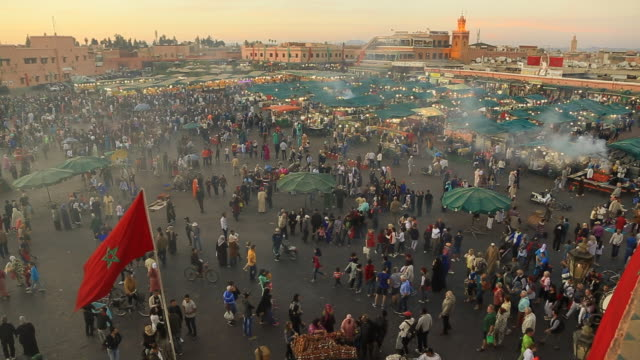 Time lapse footage from elevated viewpoint of the bustle main square of Jemaa El Fna in Marrakech city during sunset with people walking in every direction during travel vacations in Morocco.