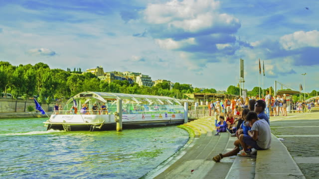 Time lapse footage of tourists activity and riverboats at Batobus Tour Eiffel terminal in Paris.