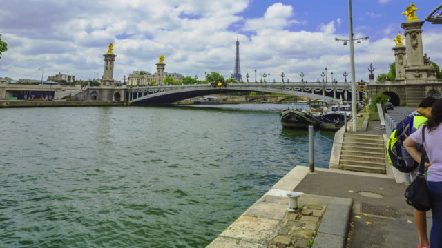 Time lapse footage of tourists awaiting river cruise boats at Batobus  terminal on River Seine in Paris.