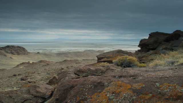 Time lapse gray clouds pass over a rocky, desolate, dramatic landscape.