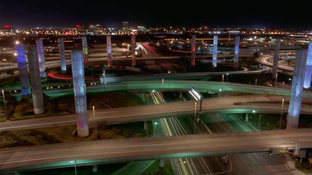 Time lapse high angle long shot pan traffic passing illuminated color pylons at entrance to LAX at night / Los Angeles