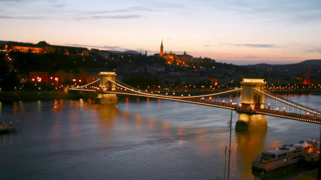 Time lapse high angle long shot Szechenyi Chain Bridge and Danube at twilight / Matthias Church in background / Budapest