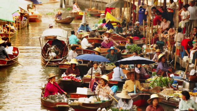Time lapse high angle medium shot women selling produce from boats in the Khlong Damnoen Saduak in the floating market / Bangkok, Thailand