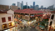 Time lapse high angle shot of busy shopping complex and outdoor market stalls in Chinatown with view of Singapore skyline in background from day to night