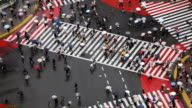 Time lapse high angle traffic and pedestrians with umbrellas in crosswalk at Shibuya Crossing / Tokyo