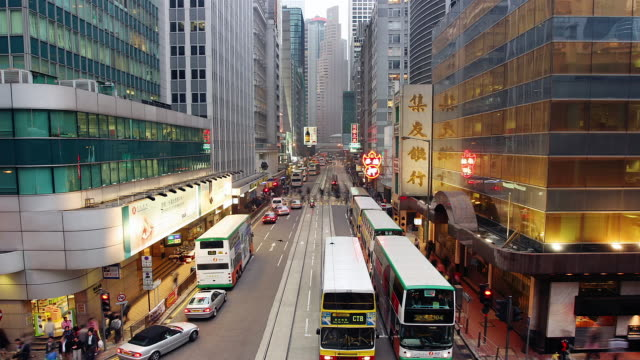 Time lapse high angle view of trams, motor traffic and pedestrians on Des Voeux Road Central / Hong Kong