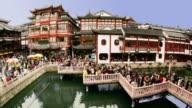 Time lapse high angle wide shot crowds on nine-turn zig-zag bridge at Yuyuan Bazaar / Shanghai