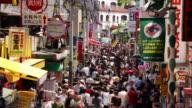 Time lapse high angle wide shot pedestrians walking along crowded Takeshita-dori in Harajuku / Tokyo, Japan