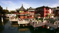 Time lapse high angle wide shot tourists crossing nine-turn zig-zag bridge at Yuyuan Bazaar / Shanghai