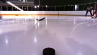 time lapse ice hockey puck point of view across ice, past hockey sticks of male players + into goal