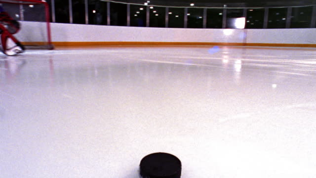 time lapse ice hockey puck point of view across ice, past male goalie + into goal