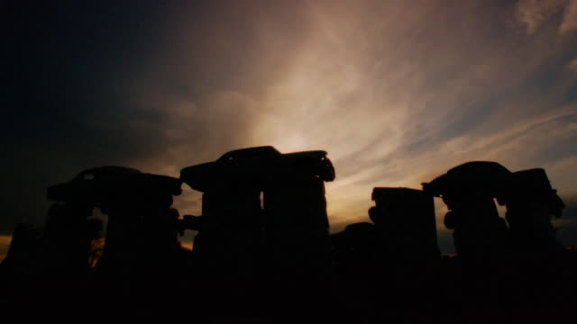 Time lapse image of clouds drifting over Carhenge sculpture (replica of Stonehenge) at sunset / South Dakota