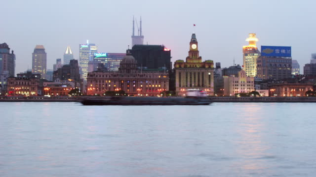 Time lapse long shot view across Huangpu River of Pudong Development Bank and Custom House on the Bund / Shanghai