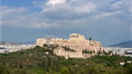 Time lapse long shot zoom in view of clouds rolling over Acropolis from Filopappos Hill / Athens