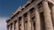 Time lapse low angle medium shot zoom out view of the Parthenon with clouds moving overhead / Athens, Greece