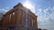 Time lapse low angle wide shot clouds rolling over Parthenon / sun shining overhead / Athens, Greece