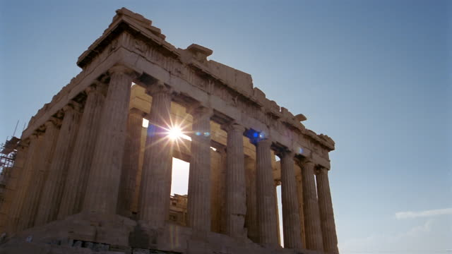 Time lapse low angle wide shot zoom out view of the Parthenon with sun in background / Athens, Greece