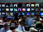ARCHIVAL Time lapse - MCU People working in Television News Room, banks of TV screens in background