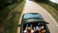 Time lapse medium shot tracking shot overhead view of women driving British car on country road in Ingatestone / Essex, UK