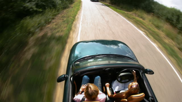 Time lapse medium shot tracking shot overhead view of women driving British car on country road in Ingatestone / Essex, UK
