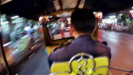 Time lapse medium shot tuk tuk passenger point of view riding through the crowded streets of Chinatown at night / Bangkok, Thailand