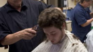 Time lapse montage young man getting haircut from barber, boy (9-10) getting haircut in background